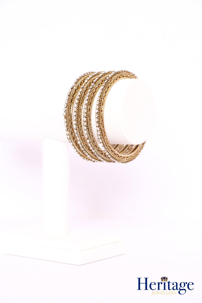 Intricately designed antique gold bangles adorned with crystals
