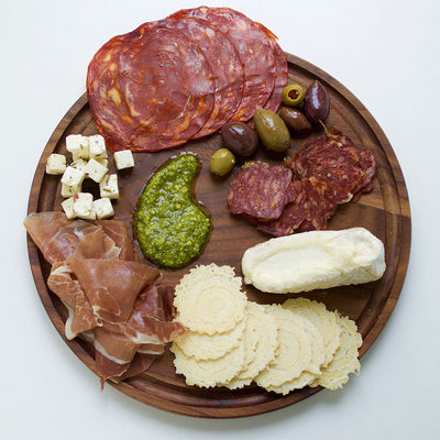 Charcuterie Spread on a Seasoned Round Cheese Board Made from Walnut Wood In USA