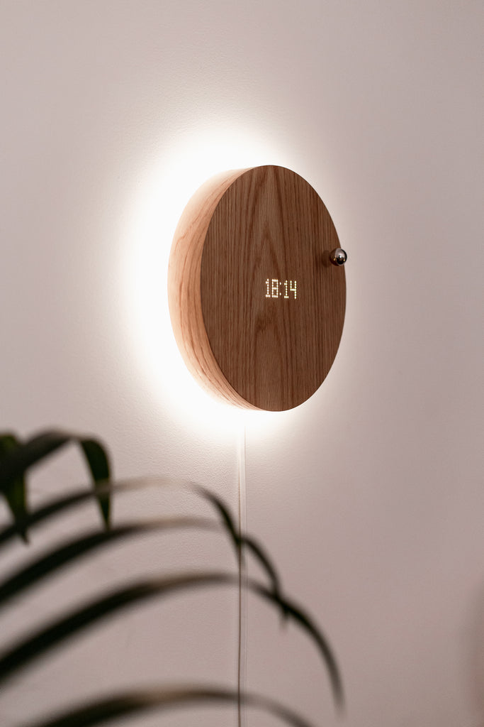 Worlds first levitating clock STORY hanging on the wall with backlight turned on