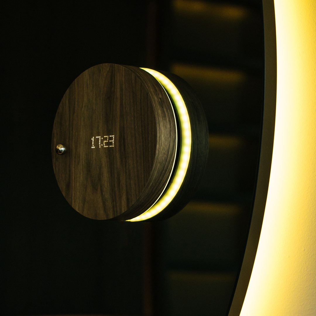 Levitating clock on a mirror with frond led on and backlight in yellow