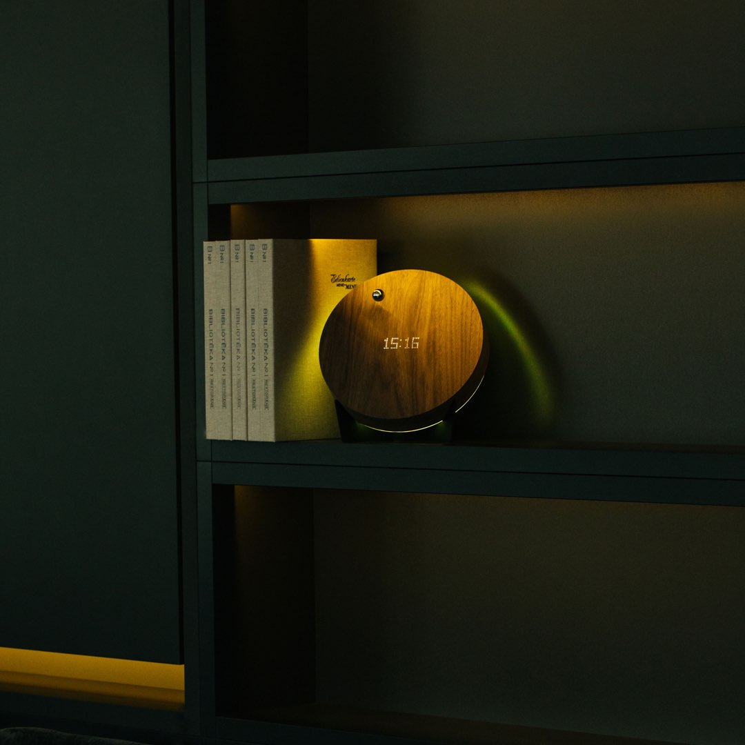 levitating clock on a shelf with books and yellow backlight