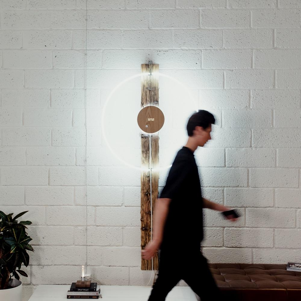 Story oak, levitating clock hanging on a white wall with man walking by in front