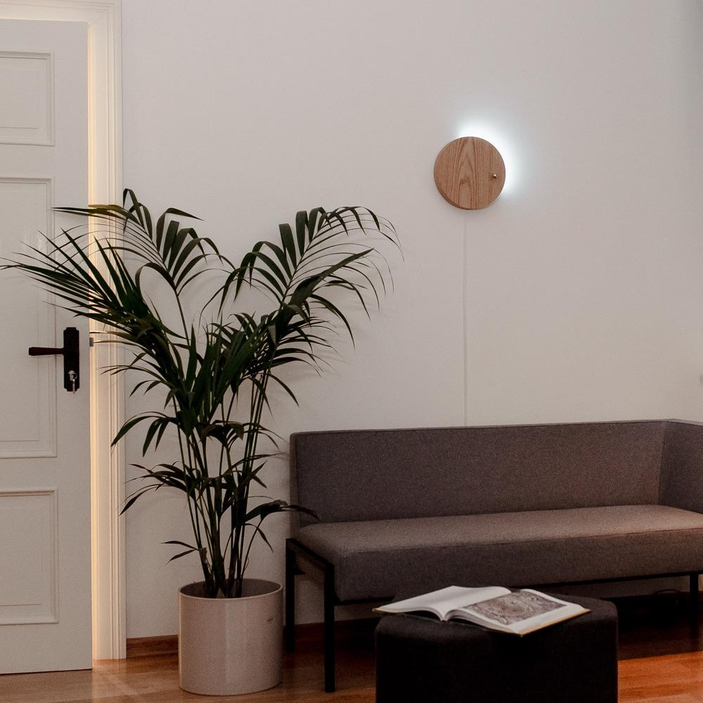 Story oak - front view of levitating clock hanging on a white wall with backlight 1/4 filled