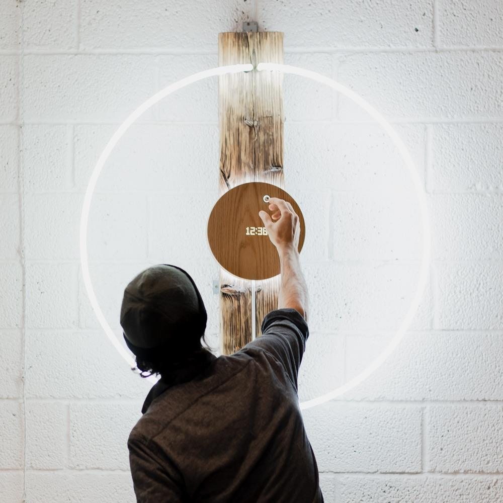story oak, levitating clock hanging on the wall and man is setting up the ball