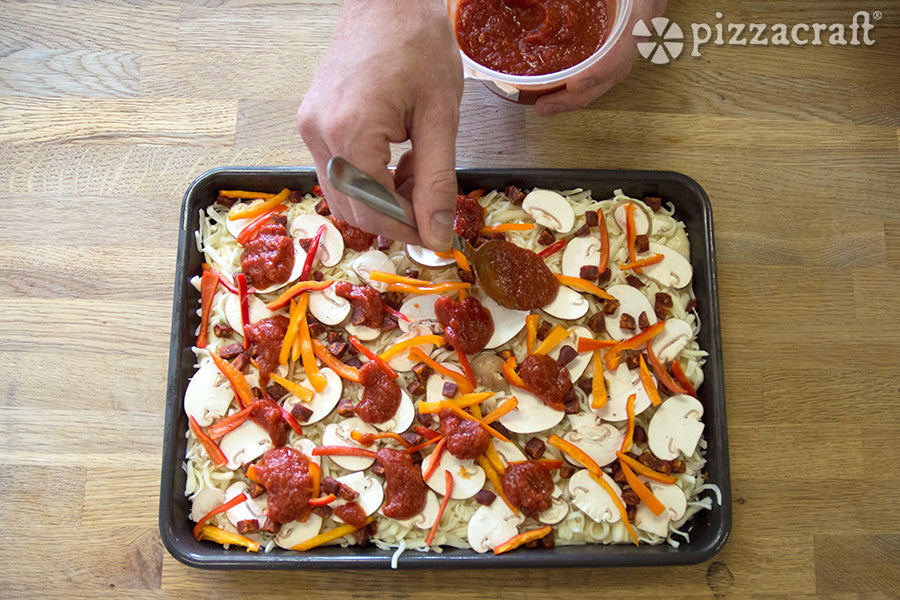 Add Spoonfuls of Pizza Sauce to the Pizza