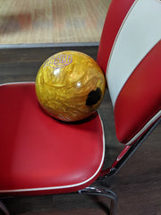Gold bowling ball with black belt mark