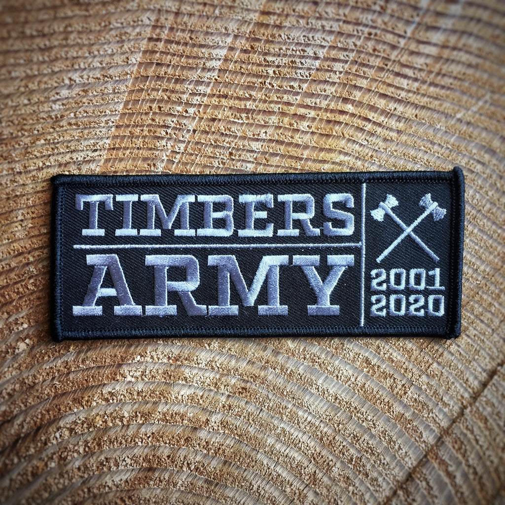 "A black rectangular patch with a black border. The left side of the patch has the word ""Timbers"" in grey above the word ""Army"" also in grey with a grey line line separating them. The words are separated from the right side of the patch by a vertical grey line. On the right side of the patch is a pair of grey crossed axes. Below the axes is the year 2001 in grey text, below that is the year 2020 in grey text."