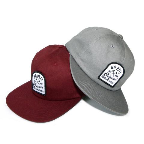 "There are two versions of the same hat. One is maroon in color and the other is grey. There is an arched patch stitched in the front center of the hats. The patch is white with a black border. The words ""No Pity"" are in black above crossed axes in black. On the left of the axes are the letters ""T-R-D"" and on the right of the axes are the letters ""M-R-K"" in black. Below the axes is the word ""Originals"" in script in black. At the bottom of the patch are the words ""Portland, Oregon"" in black."
