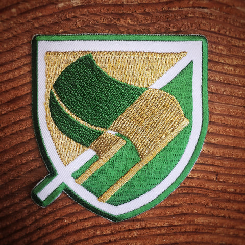 Green and metallic gold antifascist flags on a die-cut patch.
