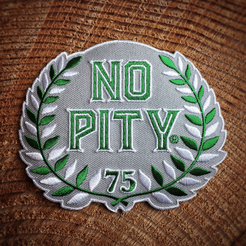 "A light grey die-cut patch with the words ""No Pity"" in green block letters with a white stroke in the middle and a white outline. At the bottom center is the number 75 in green with a white outline. Two sprigs of laurels with alternating white and green leaves starts at the bottom center. The sprigs stems are crossed at the bottom and almost fully encircle the words and number."