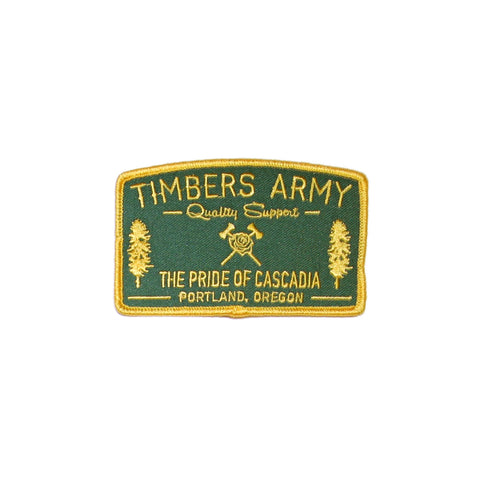 "A dark green, rectangular-shaped patch with a slightly curved top line. The Timbers Army crossed axes and rose logo in yellow is in the center of the patch. A douglas fir tree is on each side of the crossed axes and rose in yellow. The words ""Timbers Army"" are in block, yellow letters at the top of the patch; below that in script are the words ""Quality Support."" The words ""The Pride of Cascadia"" and ""Portland, Oregon"" are in block, yellow letters at the bottom of the patch."