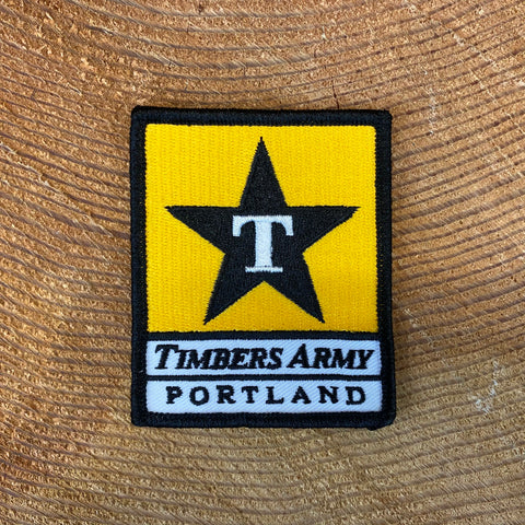 "Rectangular patch with a yellow background on the top and white background on the bottom with a black border. Inside the yellow square shape on top is a black star with a capital letter ""T"" in white. Inside the white rectangle are the words ""Timbers Army"" above the word ""Portland,"" both in black block text."