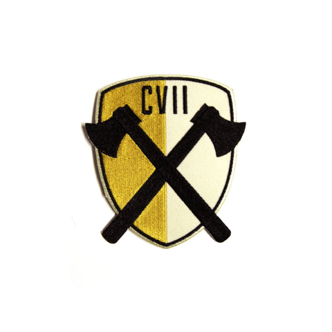 A shield-shaped patch that is gold on the left side, cream on the right side, and has a narrow black border all around it. There are two black crossed axes in the middle with black  Roman numerals CVII above the axes.