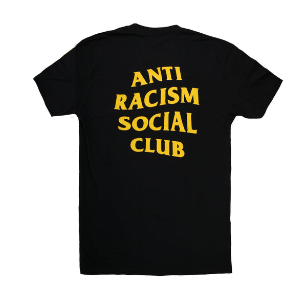 "The back of this black t-shirt has the words ""Anti-Racism Social Club"" in large yellow letters."