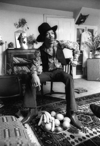 an A3 poster featuring a black and white photo of Hendrix seated in a chair in his bedroom