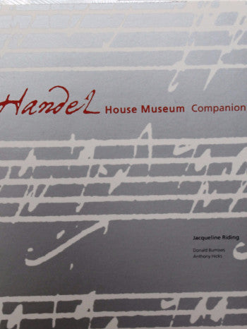 "a close up of the book cover featuring the title ""Handel House Museum Companion"" in red on a grey background with a white musical score."