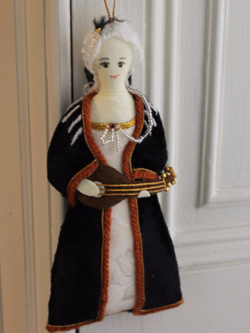 full body image of Faustina Bordoni felt hanging decoration wearing a white wig, blue and red coat, white dress, holding a lute in her hands