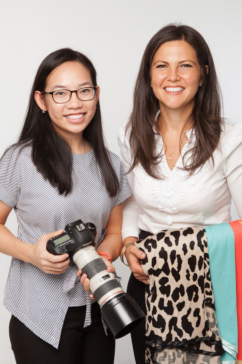 Sita, Director of Bebitza and Bree, founder of Bebitza photographed together. Sita is carrying a camera and Bree is carrying some of Bebitza's nursing covers. The two have big smiles and they make a great team!