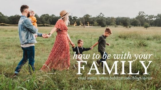 blog title: how to be with your family. Image of a dad holding a baby, while holding mum's hand. Mum is holding a toddler's hand. Toddler is holding big brother's hand.
