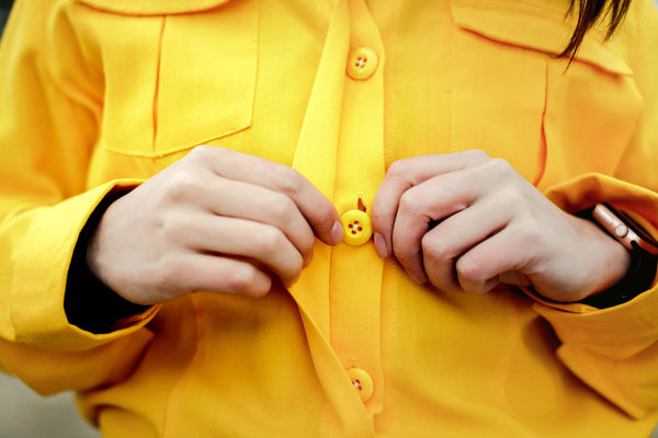 Closeup buttoning a wildland firefighting uniform shirt