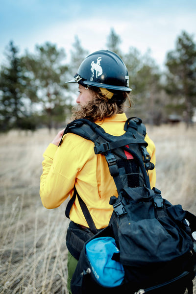 Wildland fire gear and pack on woman ready to work