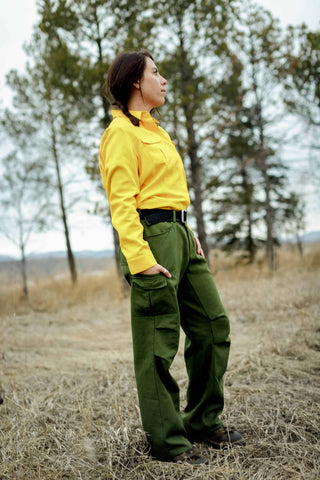 Woman firefighter looking across field towards work