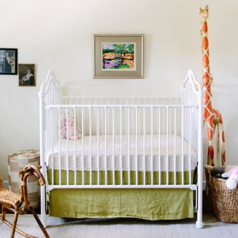 Traditional cot with green linen crib skirt
