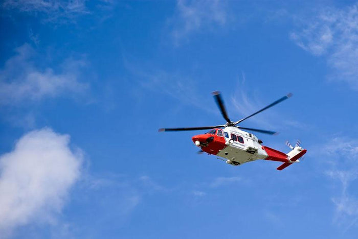 Coastguard helicopter in the blue sky Wall Mural Wallpaper