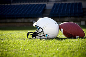 Football Helmet on a stadium field Wall Mural Wallpaper - Canvas Art Rocks - 1