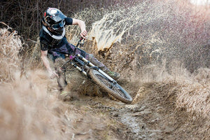 Mountainbiker rides on path in mud Wall Mural Wallpaper - Canvas Art Rocks - 1