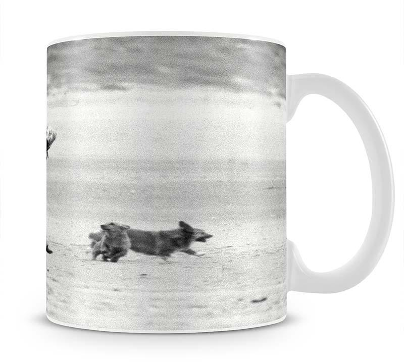 Queen Elizabeth II walking her pet corgis on a Norfolk beach Mug - Canvas Art Rocks - 1