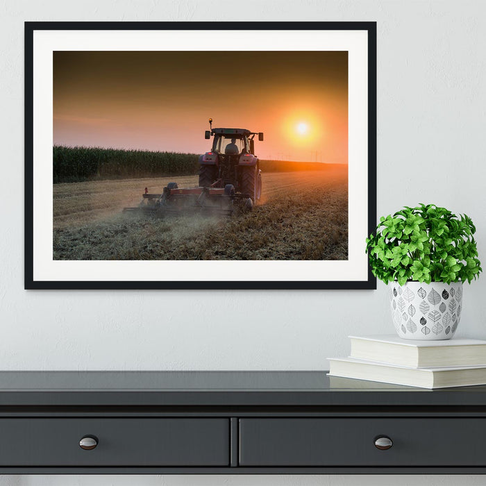 Tractor plowing field at dusk Framed Print
