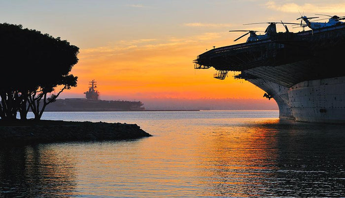 aircraft carrier in harbour in sunset Wall Mural Wallpaper