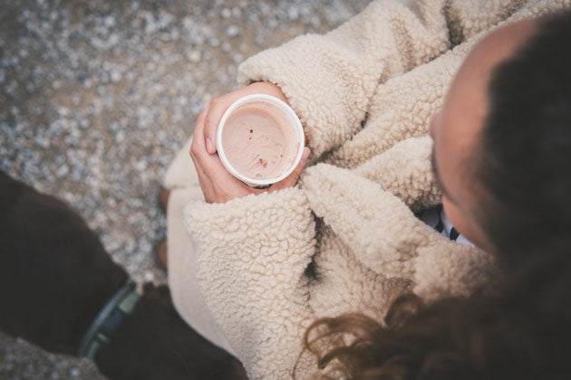 woman wearing a cute winter jacket and holding a hot chocolate