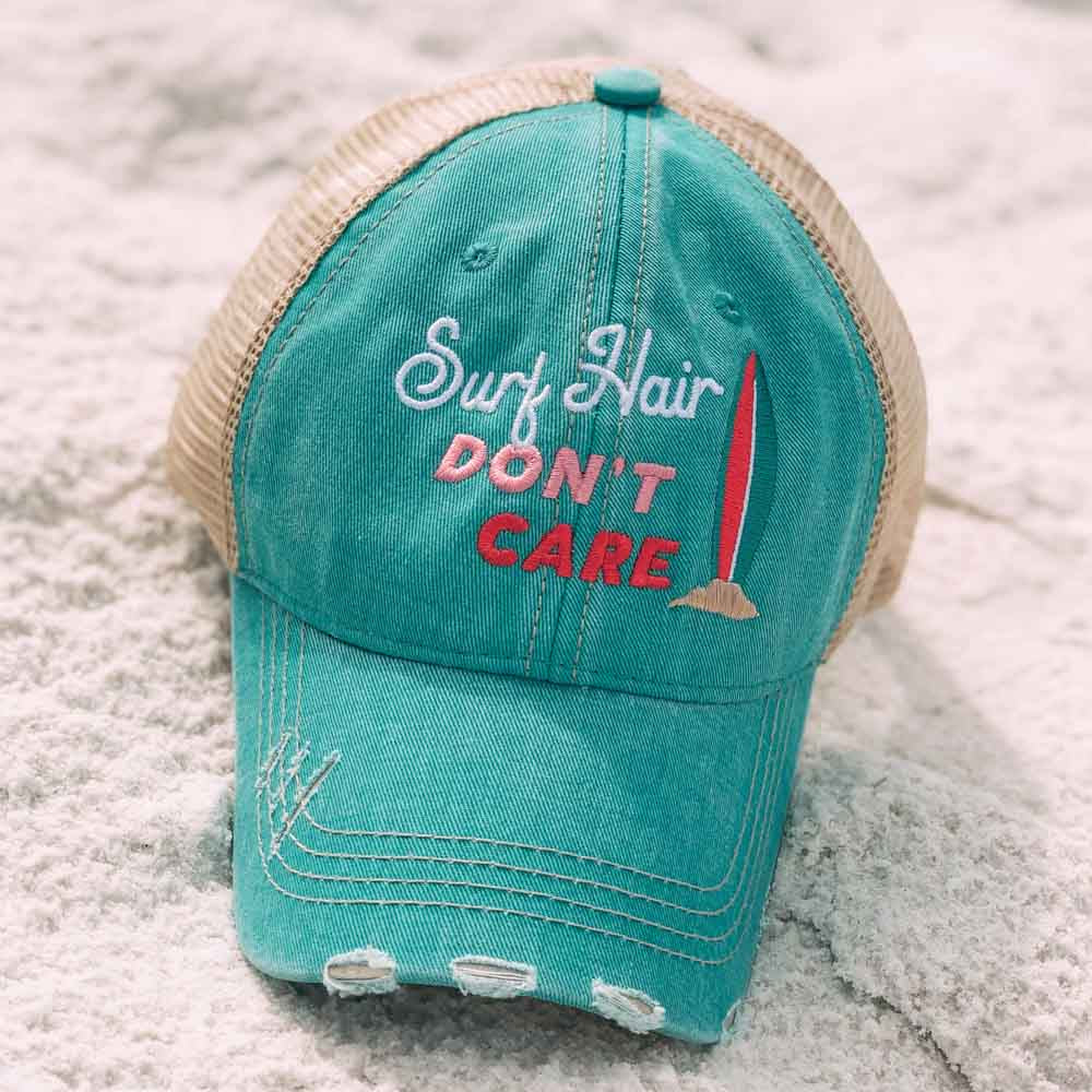 """mint distressed """"Surf Hair Don't Care"""" trucker hat sitting in the sand"""