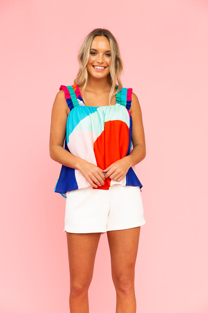 Brightly colored tank top with white shorts