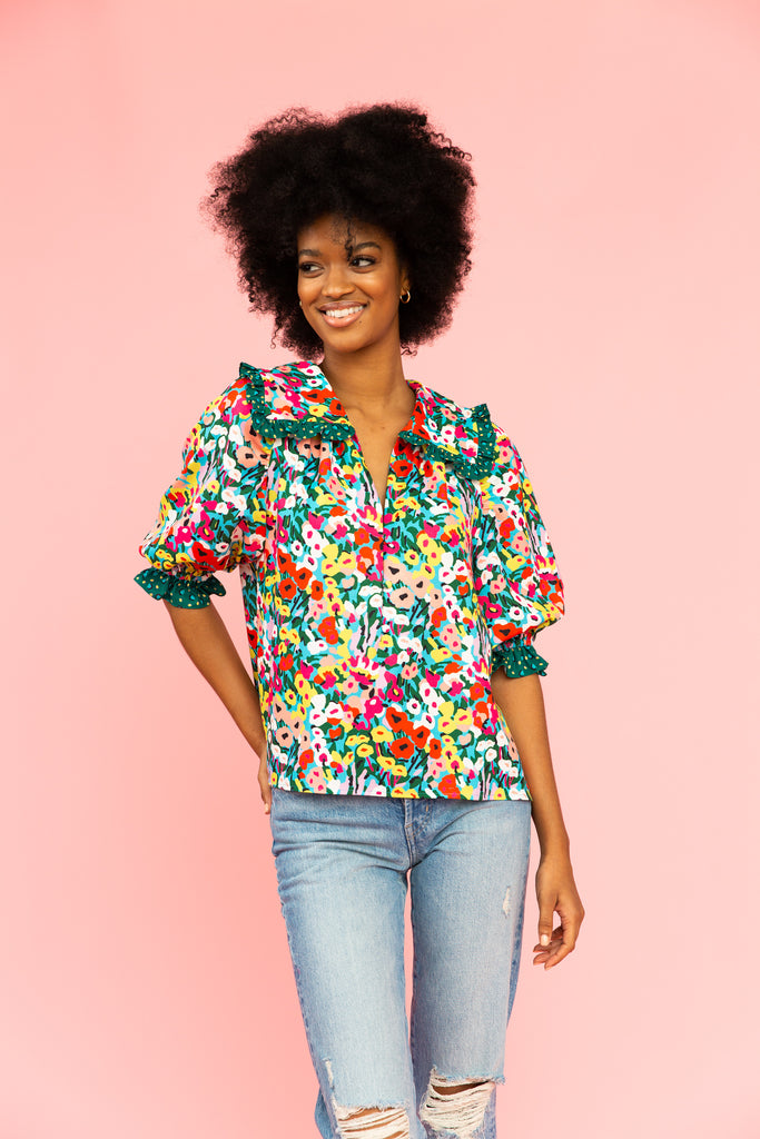 Brightly colored floral blouse with enlarged collar and distressed jeans