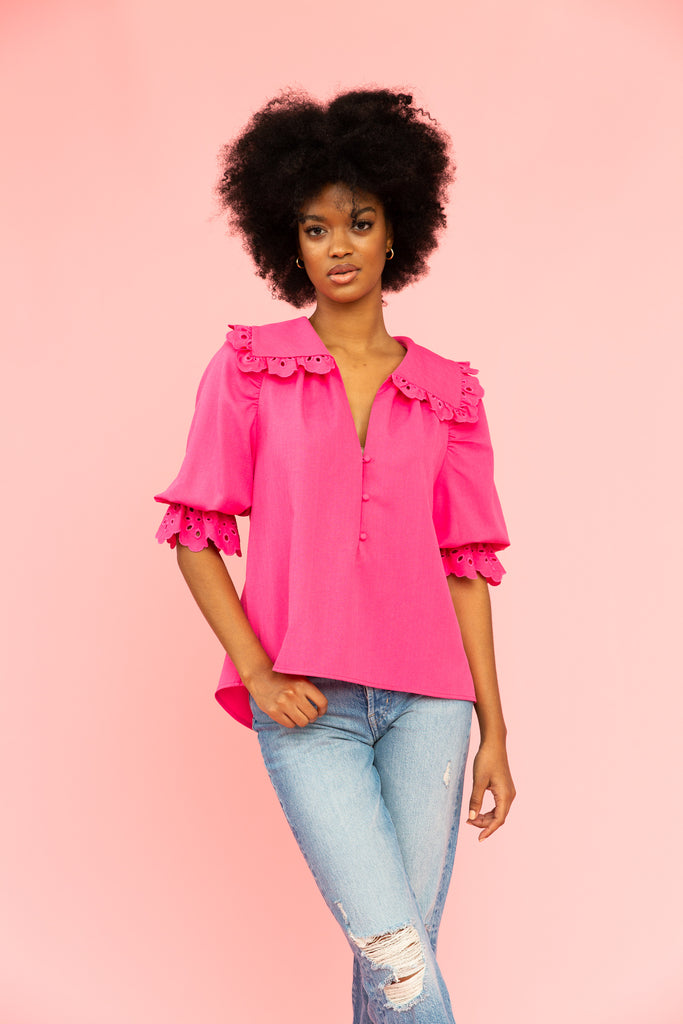 Vivid pink blouse with eyelet details and collar with distressed jeans