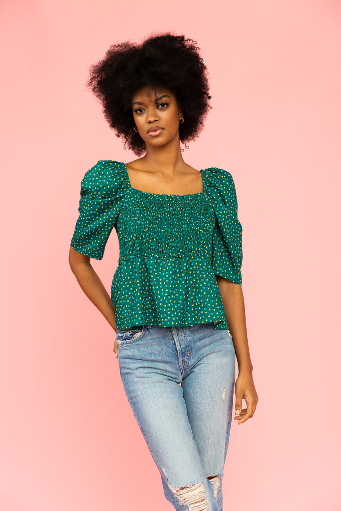 Green patterned top with smocked bodice, puff sleeve, and a peplum silhouette with distressed jeans