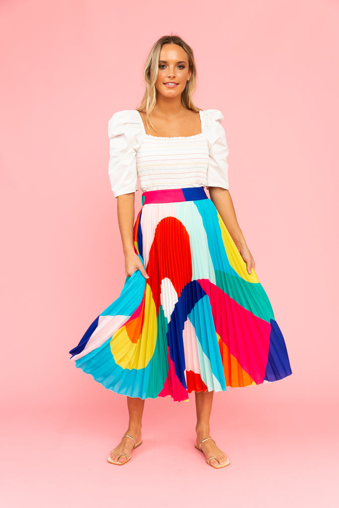 White square-neck top with brightly colored pleated skirt