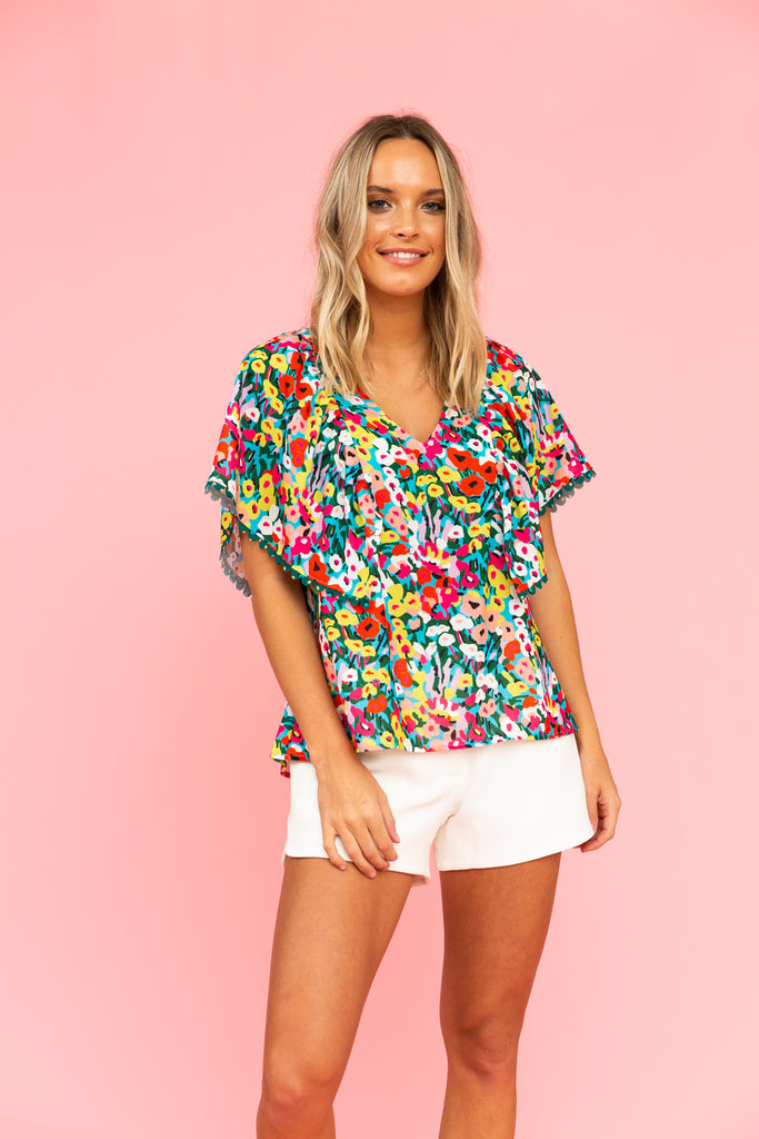 Brightly colored floral top with v-neck and white shorts