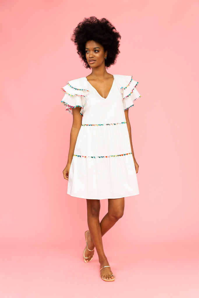 White v-neck dress with colorful trim and ruffled sleeves