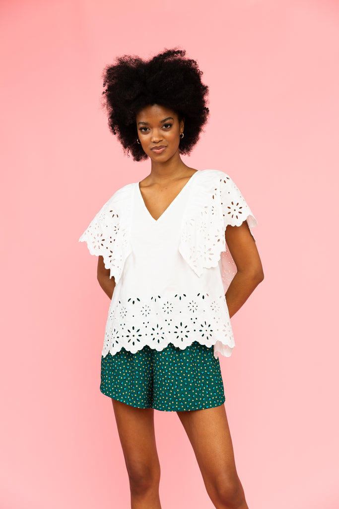 White v-neck top with eyelet details and green patterned shorts