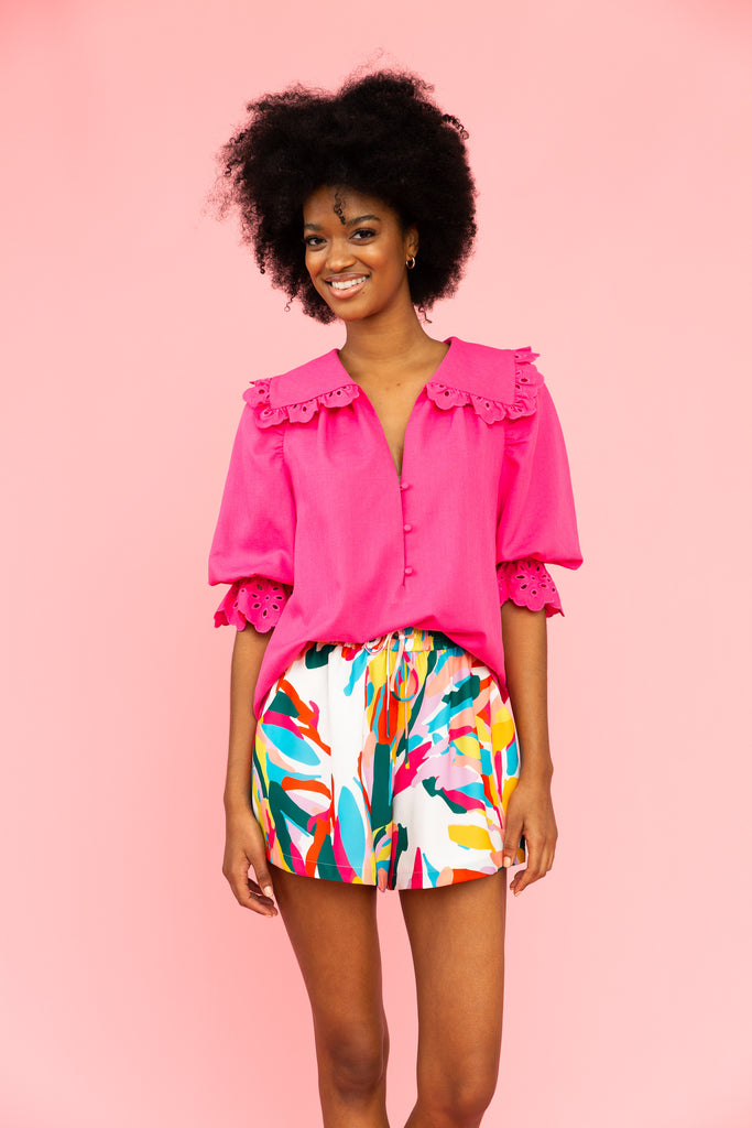 Vivid pink top with collar and eyelet details with brightly colored shorts