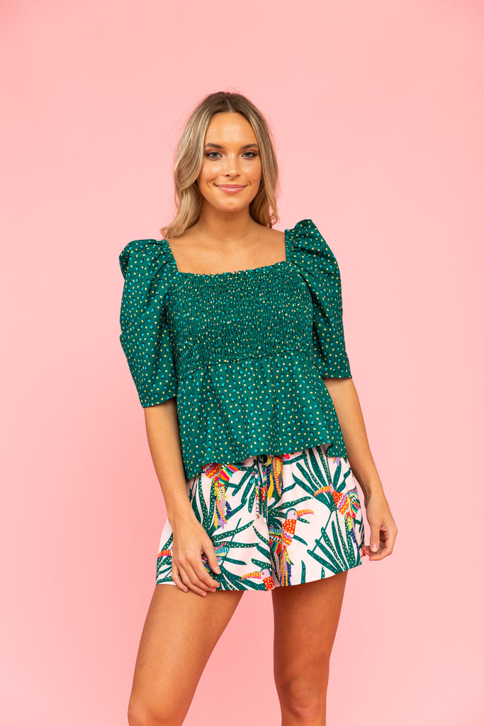 Green top with smocked bodice and peplum silhouette and shorts with parrot and leaf pattern