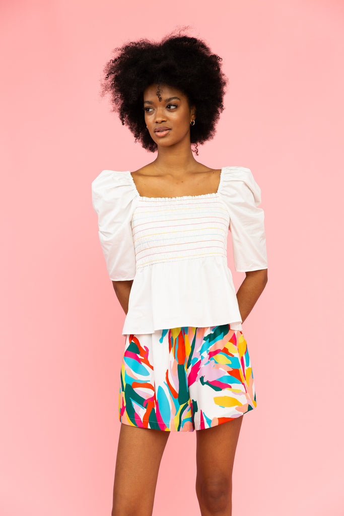 White square-neck top with smocked bodice and colorful stitching with brightly colored patterned shorts