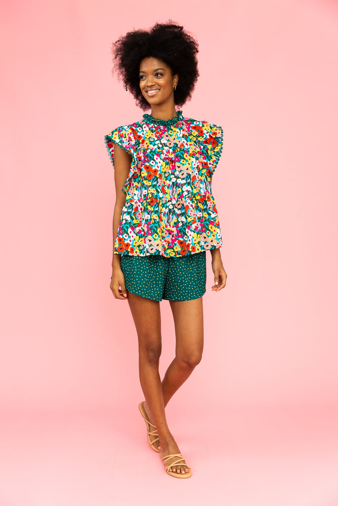 Brightly colored floral top with green patterned shorts