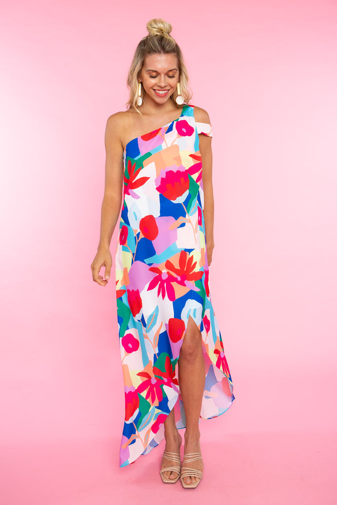 woman wearing bright floral print one shoulder maxi dress