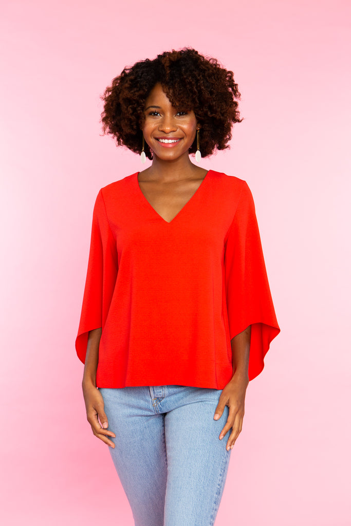 black woman wearing red v neck shirt with wide sleeves