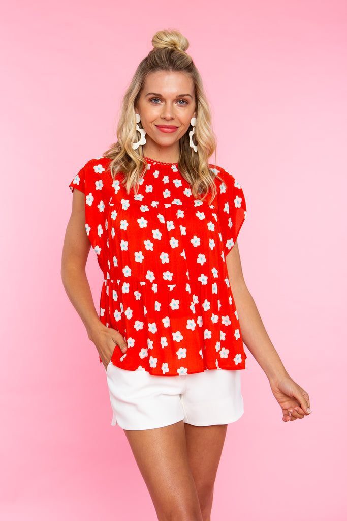woman wearing sleeveless red print trapeze top